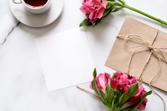 Marble desk with bouquet of flowers, pink scissors, postcard, kraft envelope, cotton branch, oat cookies, invitation card with cop. Y space for text. Flat lay stock images