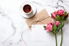 Marble desk with cup of coffee, pink flowers, postcard, kraft envelope, twine, cotton branch, oat cookies, invitation card. With copy space for text. Flat lay royalty free stock image