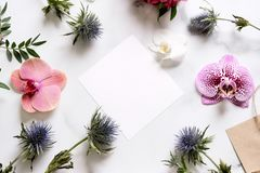 Marble desk with pink and blue flowers, postcard, invitation card with copy space for your text. Flat lay, top view. Woman`s day or mother`s day mockup royalty free stock image