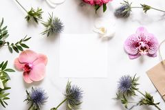 Marble desk with pink and blue flowers, postcard, invitation card with copy space for your text. Flat lay, top view. Woman`s day or mother`s day mockup royalty free stock photo
