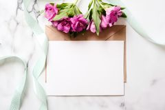 Marble desk with pink flowers, postcard, kraft envelope, twine, cotton branch, invitation card with copy space for your text. Flat lay, top view. Woman`s day stock images