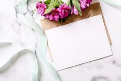 Marble desk with pink flowers, postcard, kraft envelope, twine, cotton branch, invitation card with copy space for your text. Flat lay, top view. Woman`s day royalty free stock photo