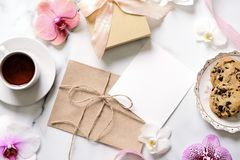 Marble desk with pink flowers, postcard, kraft envelope, twine, cotton branch, invitation card with copy space for your text. Flat lay, top view. Woman`s day royalty free stock photos