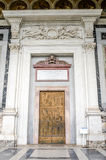 Marble door with wrought iron pattern of the saints in the church yard of the Cathedral Basilica of St. Paul Fuori le Mura in Rom. E stock image
