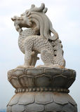 The  marble dragon sculpture. A marble  sculpture  of a little crouching dragon on a lotus shaped stone base Stock Photo