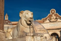 Piazza del Popolo fountain in Rome. Marble egyptian lion from People Square central fountain with city wall ancient gate, in the background, in the center of royalty free stock photos