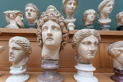 Marble faces and heads copies of ancient Roman gods and emperors on shelf. Memories about human of old world.  royalty free stock photo