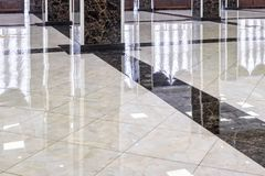 Marble floor in the luxury lobby of office or hotel. Real floor tile pattern with reflections for background. Shiny floor after professional cleaning royalty free stock image
