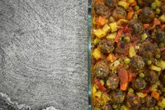 On marble floor, meatballs with vegetables, in glass baking dish royalty free stock photography