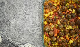 On marble floor, meatballs with vegetables, in glass baking dish stock photo