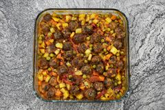 On marble floor, meatballs with vegetables, in glass baking dish royalty free stock image
