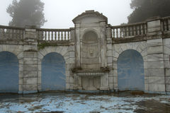 Marble fountain in disrepair. S in formal garden on rainy, foggy day Royalty Free Stock Image