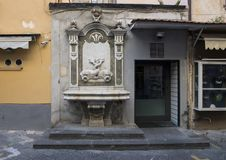 A marble fountain with entwined fish adorning a small store on a narrow street in Sorrento, Italy Royalty Free Stock Photo