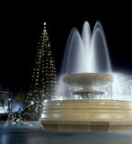 Marble Fountain at night with Christmas Tree. A Majestic fountain at Trafalgar Square in London, England. The flowing waters of the fountain are shown moving in royalty free stock photos