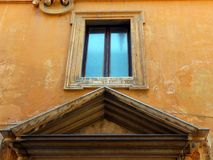 Marble Framed Window and Pediment. Ornate marble framed window and door pediment, older style stucco building, central Rome, Italy Royalty Free Stock Photography