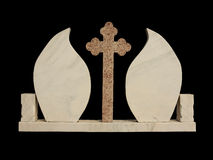 Marble grave stone on black background. Marble grave stone in shape of two leafs with a cross in the middle stock photos
