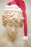 A Marble Greek Statue With Santa Hat Stock Images