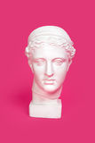 Marble head of young woman, ancient Greek goddess bust isolated on pink background Stock Photos