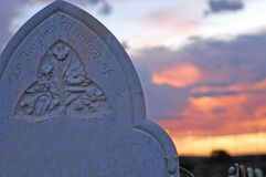 Headstone on an unmarked grave with sunset. stock image