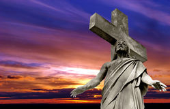 Marble Holy cross with crucified Jesus. Christ against dramatic sunset Royalty Free Stock Photo