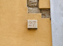 Marble house number twenty-seven. On yellow wall Stock Photos