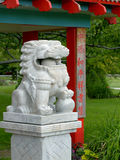 Marble lion amidst Chinese-style architecture (I). Marble lion figure amidst Chinese-style architectural elements in red and cyan with inscription commemorating Royalty Free Stock Photos