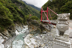 Marble lion statue in front of a red Cimu Bridge at Taroko Royalty Free Stock Photo