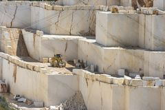 Marble mine with working tractor. Marble block industry while working royalty free stock image