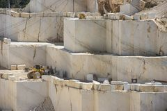Marble mine with working loader. Marble block industry while working with heavy machines stock images