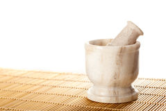 Marble mortar with pestle. On bamboo mat Royalty Free Stock Images