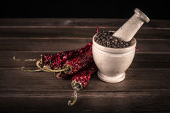 Marble mortar with spices black pepper and red hot pepper Stock Photography