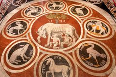 Marble mosaic with Rome and Siena symbols on floor of 14th century Duomo di Siena. SIENA, ITALY - SEP 22: Marble mosaic with Rome and Siena symbols on floor of stock photo