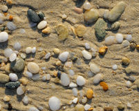 Marble pebbles scattered on the sand. As a background Stock Image