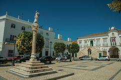 Marble pillory with sculpture in square and City Hall in the back. Marble pillory with sculpture in square, old buildings and City Hall in the back, in a sunny royalty free stock photo