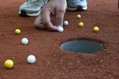 A marble player shooting marbles to the hole Royalty Free Stock Photography