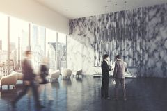 Marble reception counter, office, side, people. Side view of a marble reception desk standing in a marble wall office lobby with a white armchair in the waiting Royalty Free Stock Images