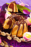 Marble  ring cake for easter. Marble ring cake  poured with chocolate on easter table in purple color Stock Image