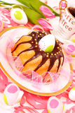 Marble  ring cake for easter. Marble ring cake  poured with chocolate on easter table in pink color Stock Photos