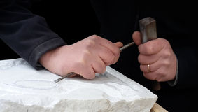 Marble sculpting. Man hands sculpting a piece of white marble Stock Photography