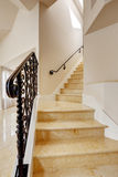 Marble staircase with black wrought iron railing Royalty Free Stock Photo