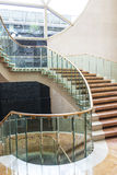 Marble Staircase. A luxurious winding marble staircase with glass railing Stock Photo