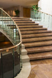 Marble Staircase. A luxurious winding marble staircase with glass railing Royalty Free Stock Images