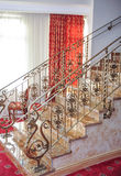 Marble stairs with golden metal handle leading up. Luxurious stairs with red curtains on background Royalty Free Stock Photo