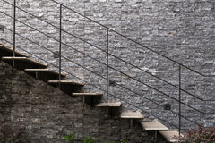 Marble stairs with metal handrail on granite wall Royalty Free Stock Photo