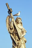 Marble statue of an Angel, in Rome, with cross and seagull. A marble statue of an Angel near Saint Angel Bridge in Rome, with a cross in arms and a seagull on royalty free stock image