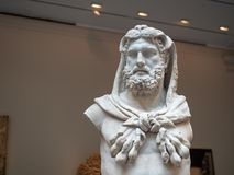 Marble statue of a bearded Hercules weating lion skin, made around 1st century A.D. in the Roman times. A marble statue of a bearded Hercules weating lion skin royalty free stock images