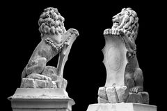 Marble statue of lion holding a shield in its paws. Regal lion leaning on empty heraldic shield isolated on black. Stock Photo