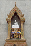 Marble Statue on Wat Indravihan. A marble statue of an enlightened one in a gold enshrined frame on the outside of a prayer hall at Wat Indravihan in Bangkok Royalty Free Stock Photo