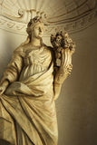 Marble statue - woman with cone of flowers Stock Images