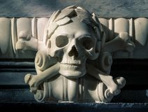 Marble stone skull and bones sculpture. Baroque sculpted marble skull and bones ornament, clair obscure, laurel crown royalty free stock photos